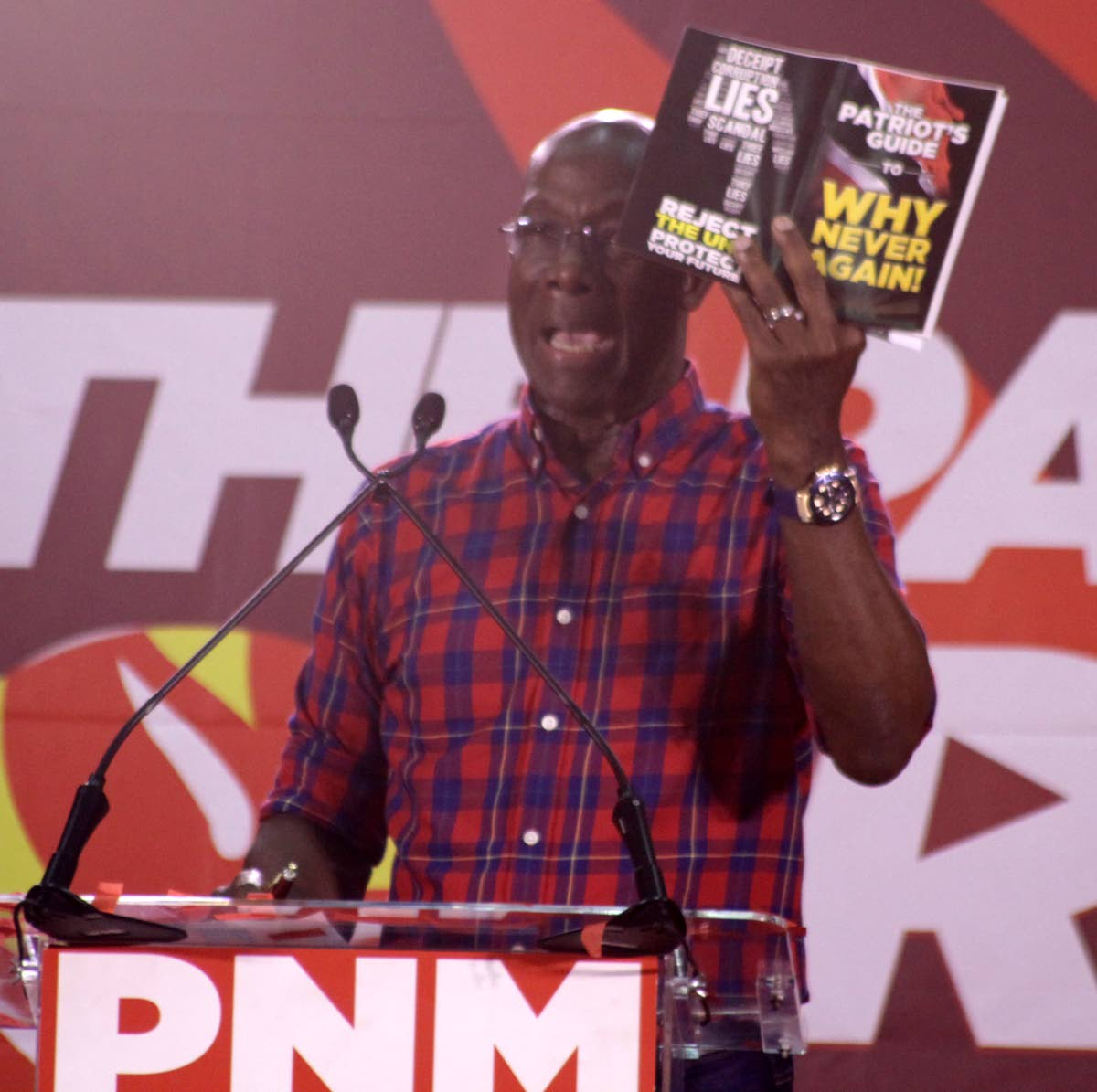 "NEVER AGAIN:  PM Dr Keith Rowley with PNM publication, ""Why Never Again"" at St Francois Valley Girl's College, Belmont, Thursday night. PHOTO BY ROGER JACOB"