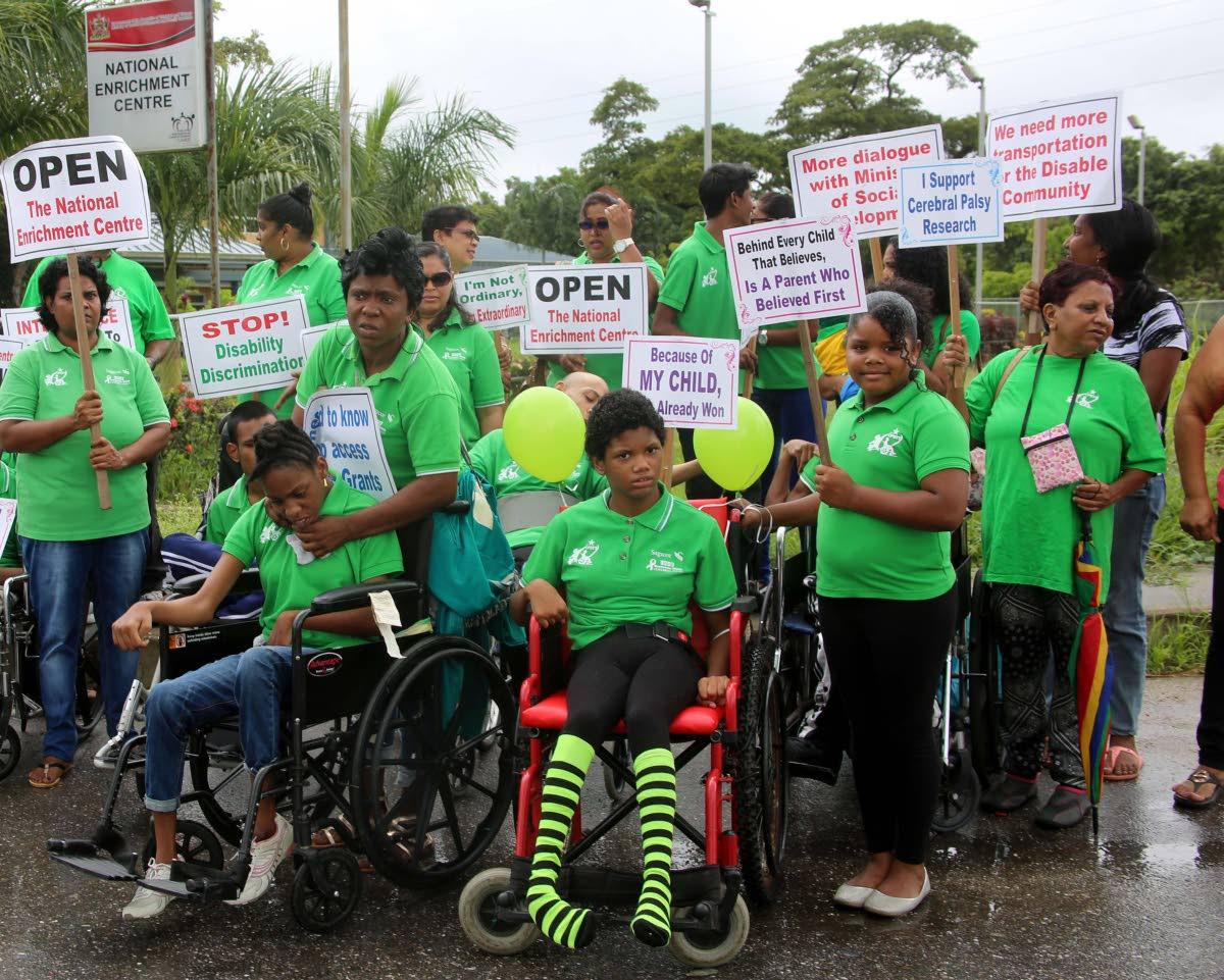 PROTEST: Parents with their physically challenged children protest yesterday for the opening of the newly built Centre for Persons with Disabilities, Chase Village, Carlsen Field. PHOTO BY VASHTI SINGH