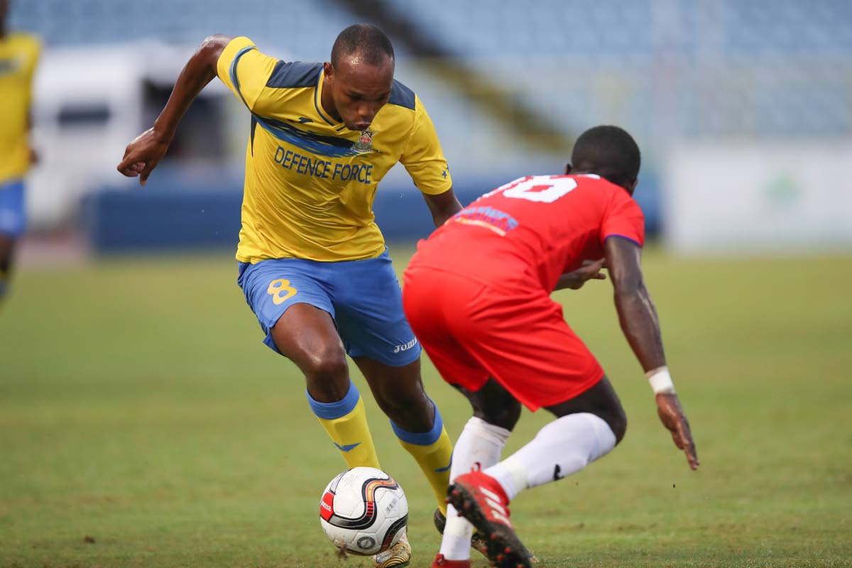 Defence Force Brent Sam attempts to dribble past Morvant Caledonia Travell Edwards in a First Citizens Cup semifinal at the Hasely Crawford Stadium, Mucurapo, Friday.