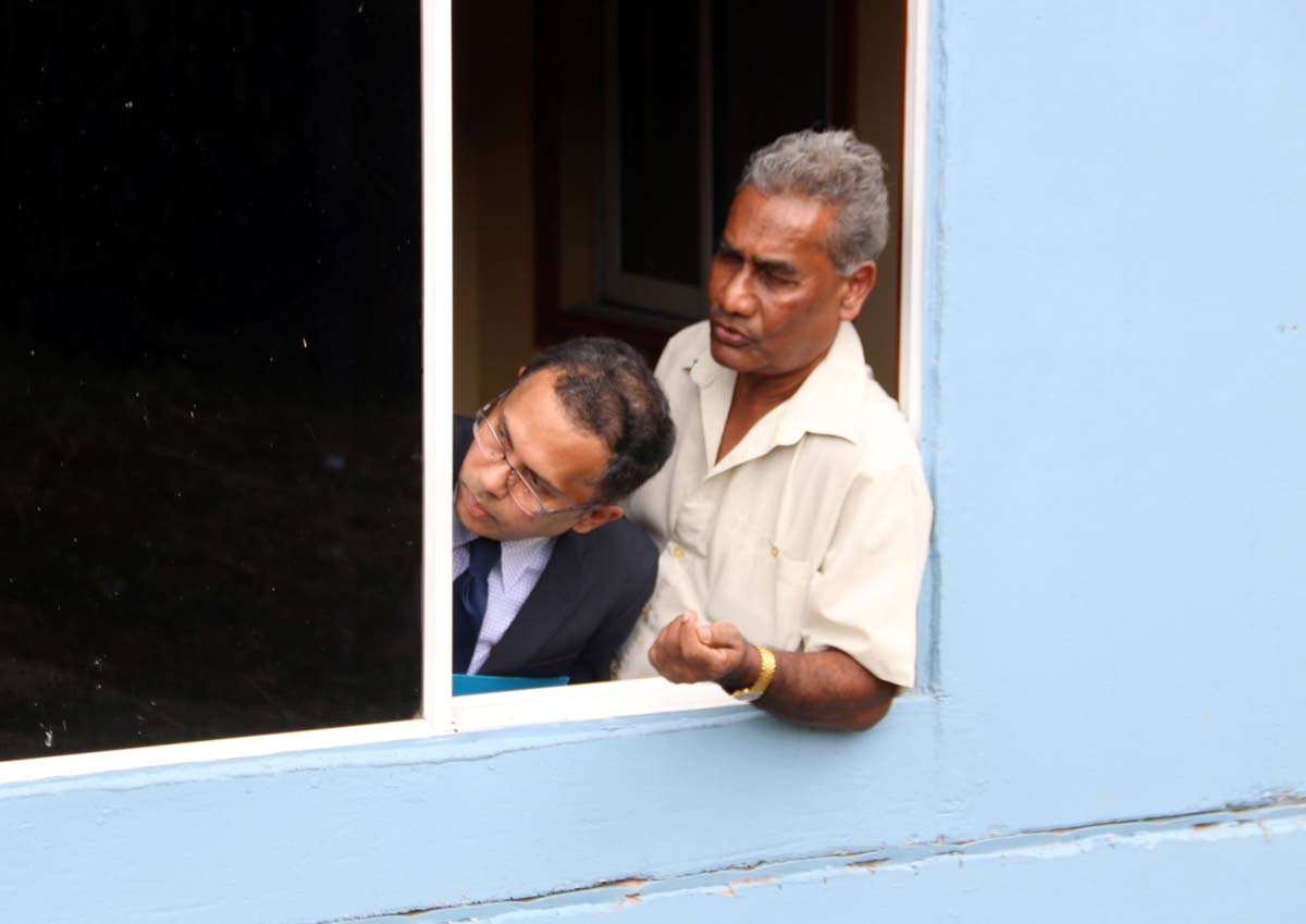 Justice Ronnie Boodoosingh, left, peers out a window yesterday as he convened court at a mandir near Princes Town which is the subject of an ongoing land dispute case.