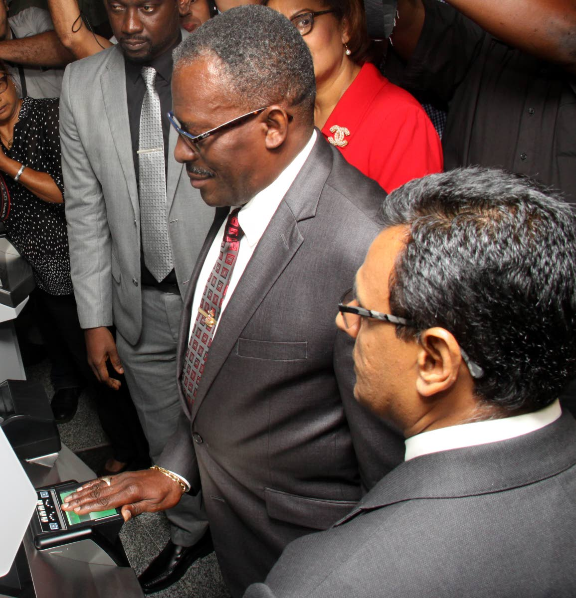 Minister of National Security Edmund Dillon tests the newly launched Automated Boreder Control System at the Piarco International Airport. Minister of Works & Transport Rohan Sinanan, right, looks on. PHOTO: ANGELO M. MARCELLE