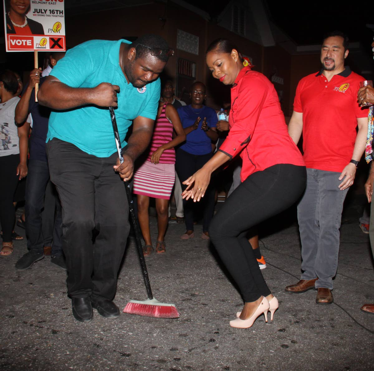 SWEEP THEM: PNM councillor-elect Nicole Young dances while PoS Deputy Hillan Morean sweeps the ground to signify the party's dominance in the Belmont East by elections.