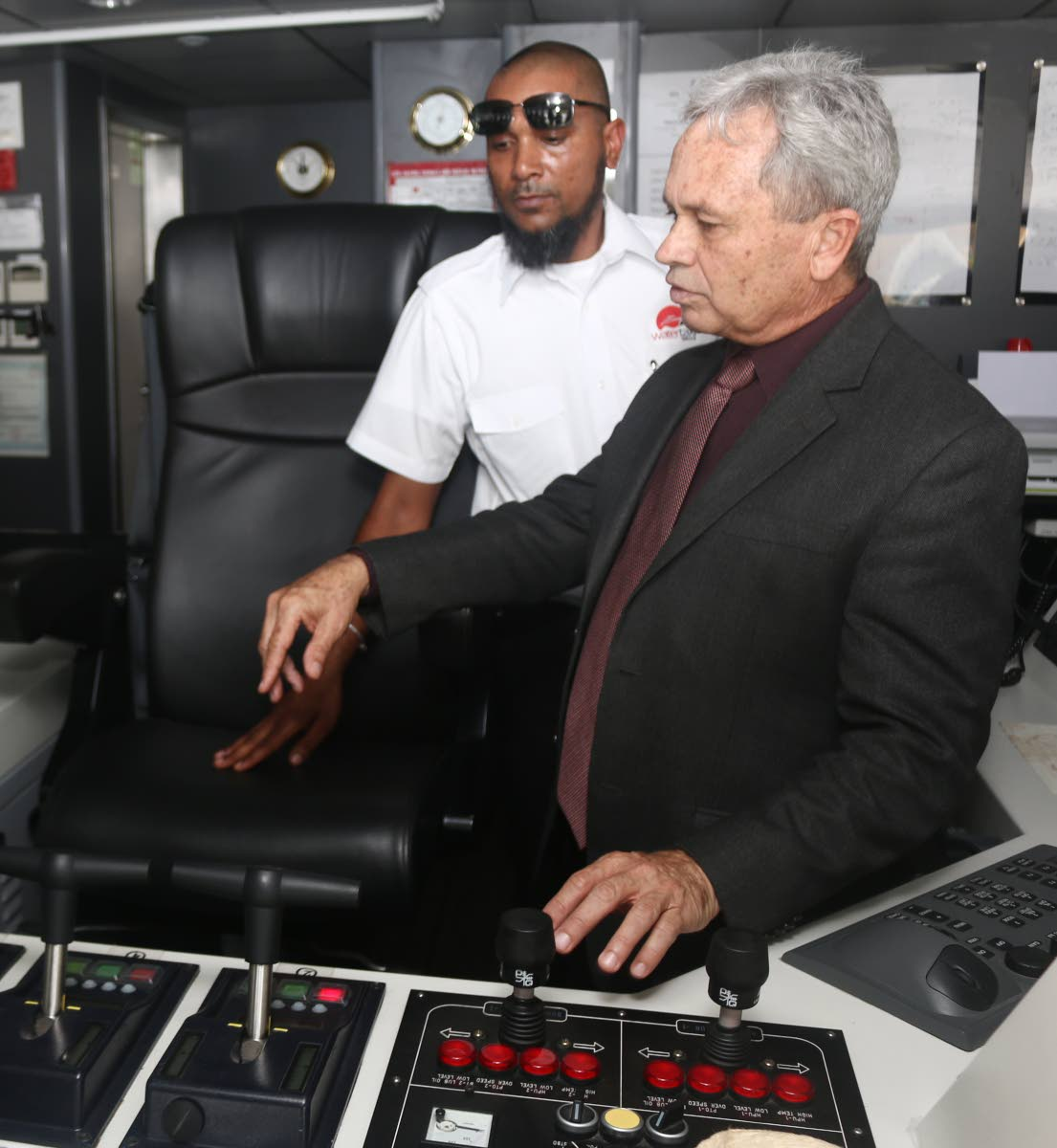 Port captain Alister Khan and Minister of Finance Colm Imbert tour the captain's bridge on board the Galleons Passage. Photo:  Xavier Sylvester