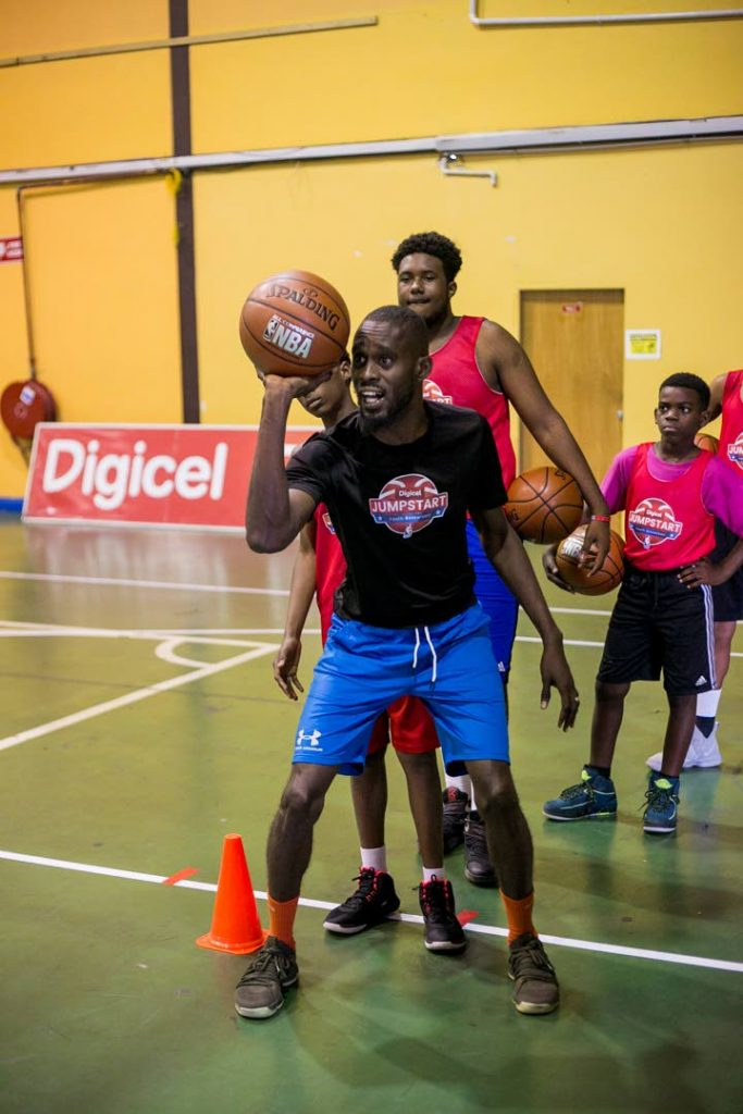 Kern George, front, head coach of Stories of Success Academy, demonstrates a shooting drill at the Digicel Jumpstart clinic earlier this year.