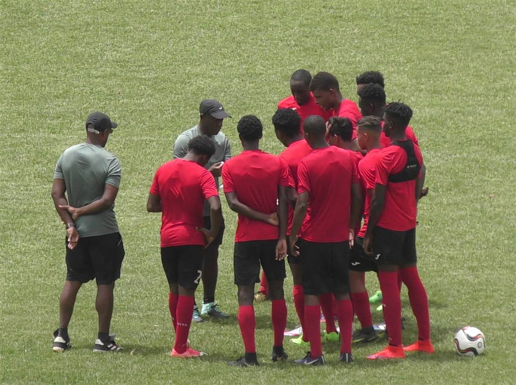 National Under-20 coach Russell Latapy, centre, talks to his players following a training session recently.