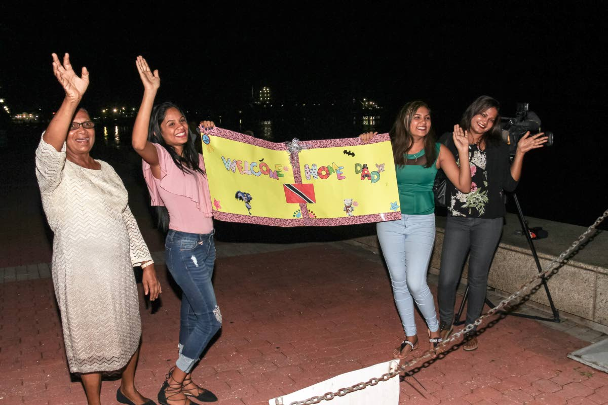 WELCOME HOME: Krystle Khan, right, her mother in law Madonna Khan, left, and Krystle's daughters Aenea, 2nd from left, and Alisha await the arrival of their loved one, Galleons Passage captain Allister Khan on Monday night at the the International Waterfront Centre in Port of Spain. PHOTO BY JEFF K. MAYERS