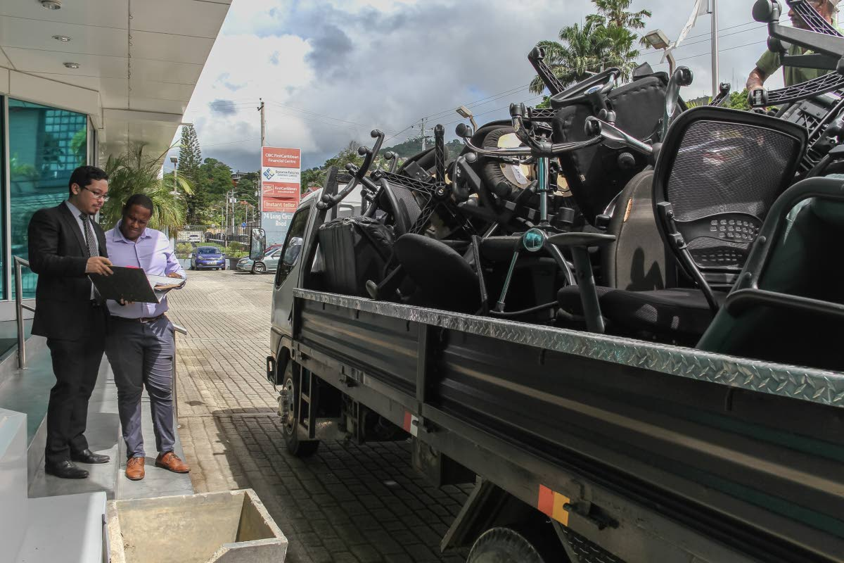 OFF IT GOES: Attorneys Joel Rooper (right) and Justin Leung go through a list of items as the are loaded onto a truck, as a result of a court judgement between Prudecon Limited and EFCL, at  Long Circular Road, Maraval, on Wednesday. PHOTO BT JEFF K MAYERS