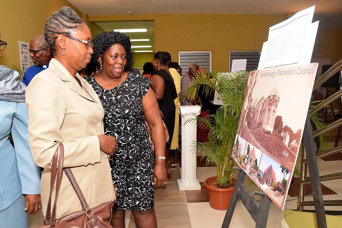 Reverend Janice Soyer- Delaney, left, and Reverend Esther Moore-Roberts, chairman of the Tobago Christian Council, Moravian Church view a photograph of the evolution of the Scarborough Methodist church at the opening of the exhibit