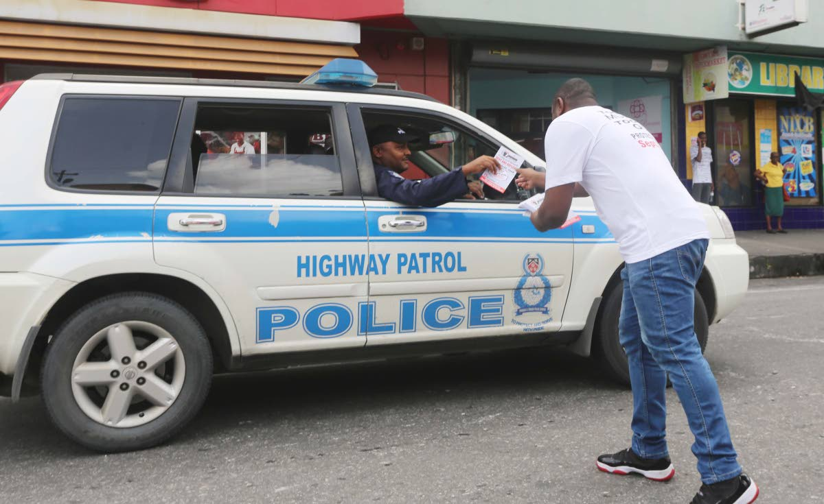 CRIME PLAN: A member of the Joint Trade Union Movement passes a flyer to police officers on High Street, San Fernando on Thursday.