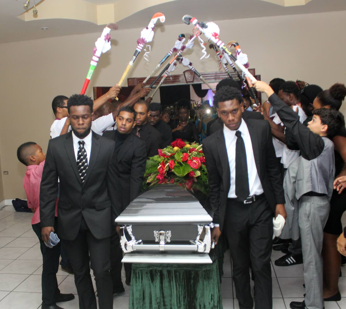 The brothers of Kwasi Emmanuel, Keiron, left, and Kristien, right, carry his casket at his funeral service at Faith Assembly Church yesterday in Five Rivers. PHOTO BY ENRIQUE ASSOON