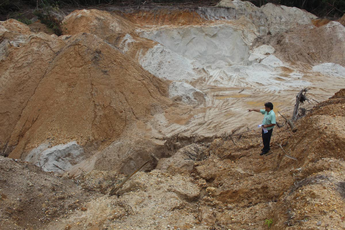 BARREN LAND: Newsday reporter Sean Douglas points to barren soil in a crater left by illegal quarrying at the Melajo Nature Reserve. PHOTO BY ENRIQYE ASSOON
