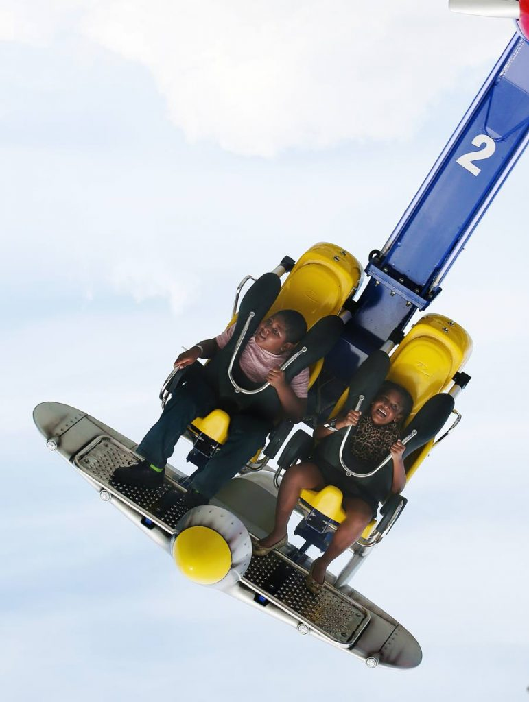 UP IN THE AIR: In this July 2017 photo, two courageous youngsters try out the Dragon Fly ride at Five Islands Water and Amusement Park yesterday. The Park, located in Chaguaramas, opened to the public on August 5, 2017. Photo by Azlan Mohammed.