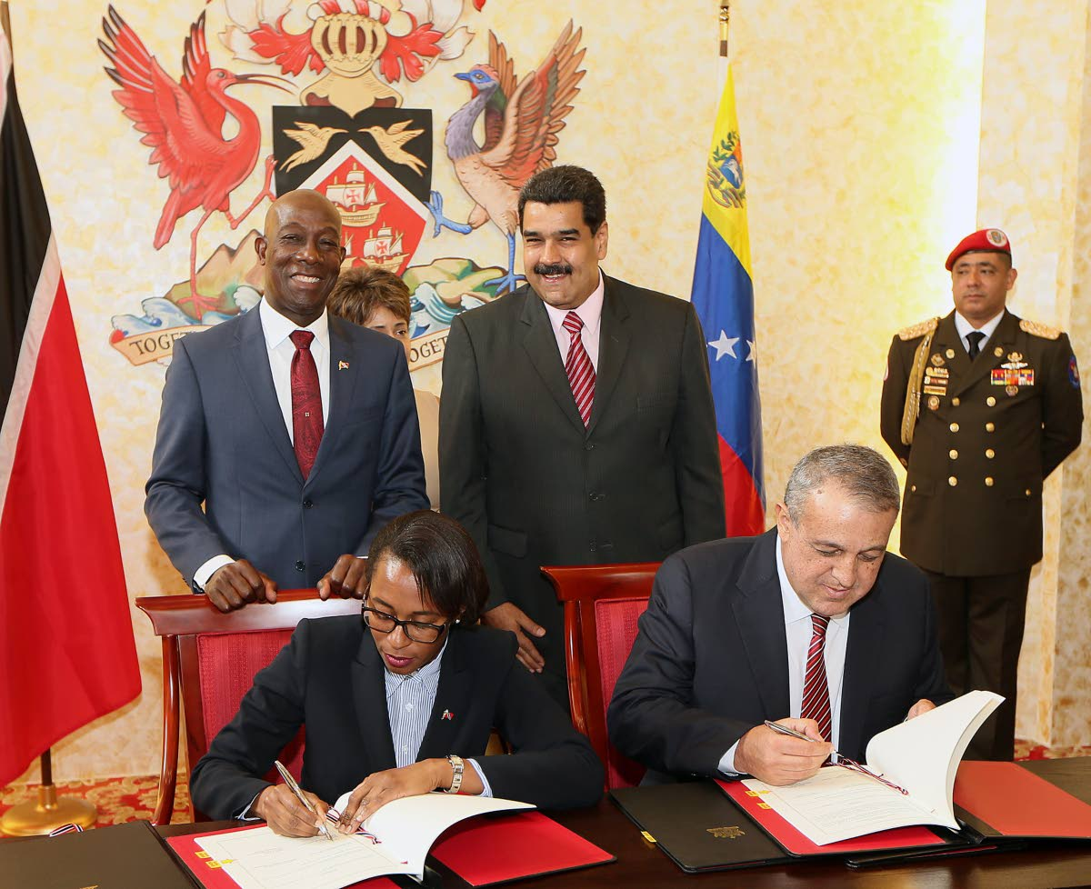 Venezuelan president Nicholas Maduro, right, and Prime Minister Keith Rowley in background looks on while Minister of Energy Nicole Olivere and   Venezula's Minister of Petroleum and Mining Eulogio del Pinosigns agreements document following  the  bi lateral meeting  TT government and Venezuela  at the Diplomatic center St Anns in May 2016. PHOTO BY AZLAN MOHAMMED