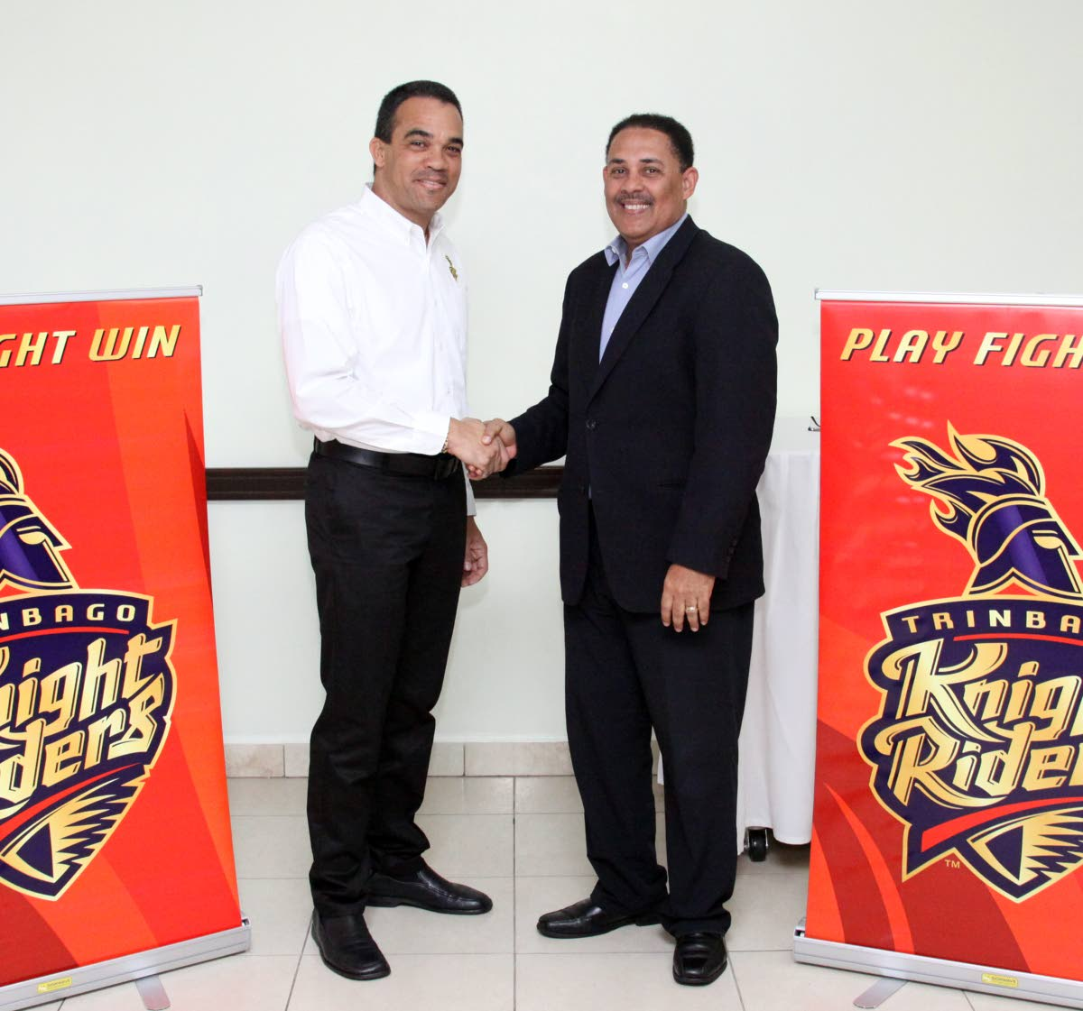 Trinidad Knight Riders Manager, Paul Skinner, left and Massy Technologies InfoCom CEO David Belgrave shake hands on a sponsorship agreement at the President's Box, Queen's Park Oval, St Clair in July. Photo by Angelo Marcelle