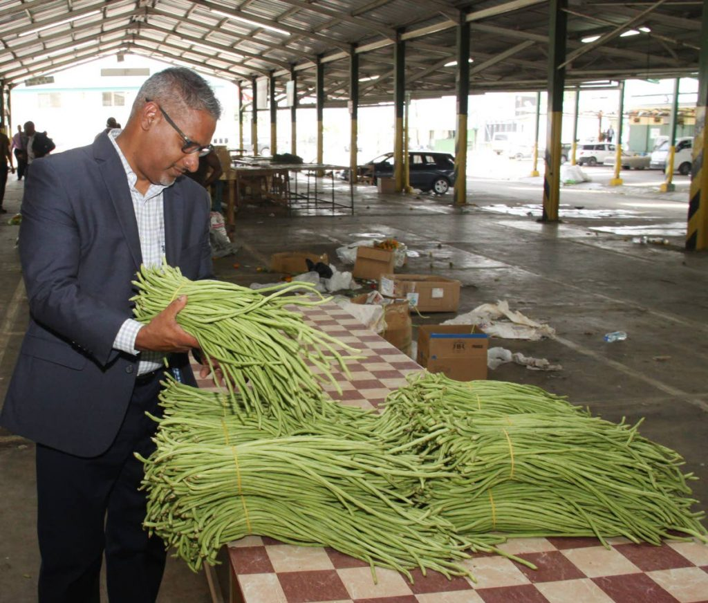 In this file photo, Minister of Agriculture, Clarence Rambharat examines bundles of bodi at the Norris Deonarine Wholesale Market in Macoya.