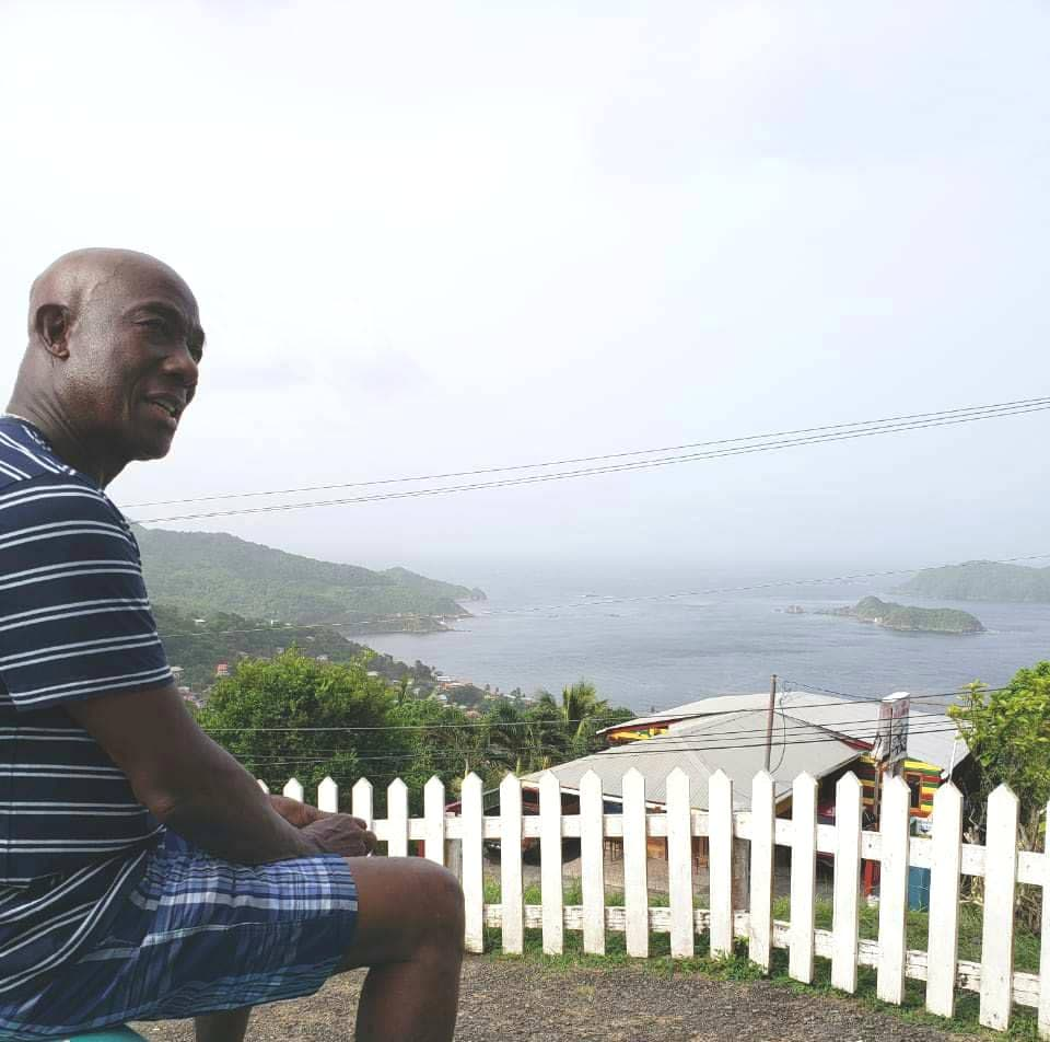 RELAXING TIME: PM Rowley relaxes and takes in the view of the sea.