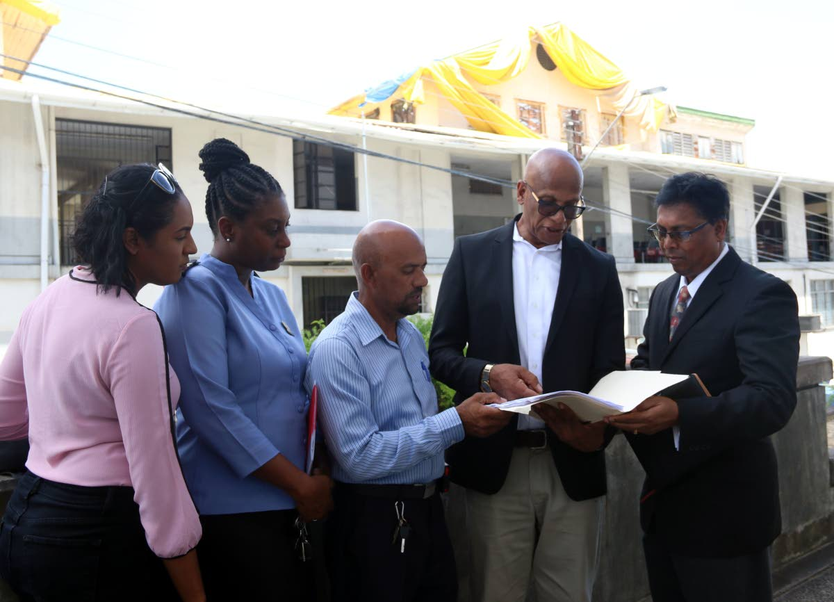 CONCERN: (from left) Building inspector Candice Brooker, public health inspector Natasha Howard, building inspector David Mohammed, mayor Junia Regrello and attorney Ramesh Deena look at some documents in front of the dilapidated San Fernando Magistrates' Court on Wednesday.