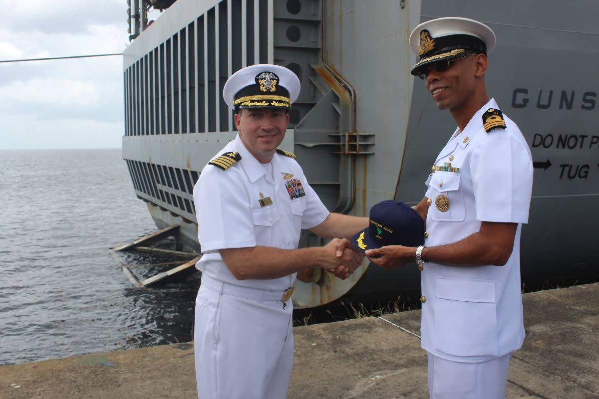 GIFT: Commanding officer of the US Navy ship USS Gunston Hall Capt Brian Diebold, left, presents a cap  to Acting Commander of the TT Coast Guard Don Polo yesterday at the Port of Spain docks.