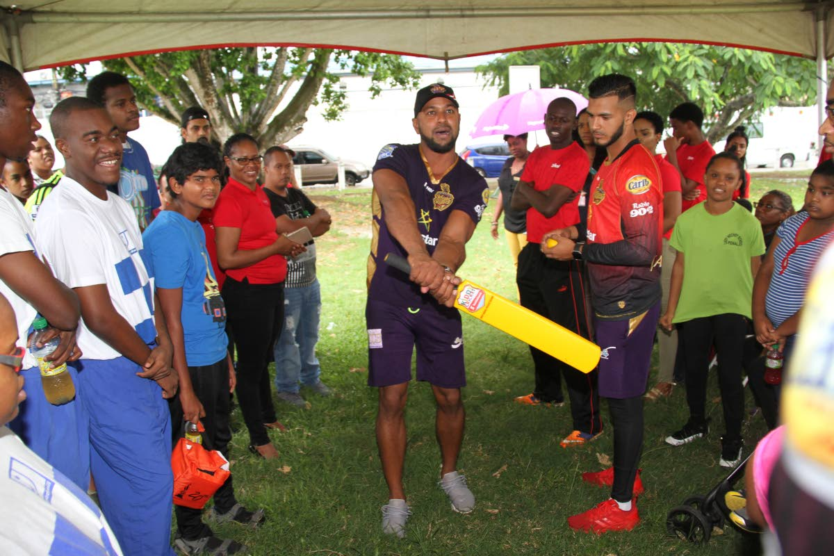 Coach of Trinbago Knight Riders, Imran Jan and player Amir Jangoo, right, demonstrate a batting technique at the Digicel Youth Cricket Series, at Nelson Mandela Park, St Clair, yesterday. Photo: SUREASH CHOLAI