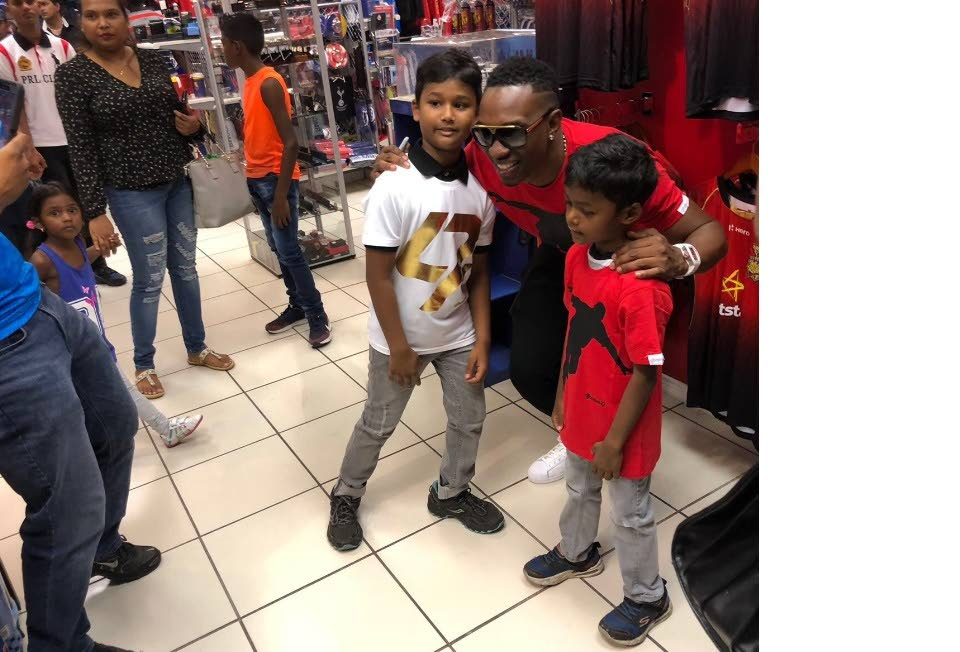 Trinbago Knight Riders captain Dwayne Bravo, centre, poses with fans wearing his official djbravo47 t-shirts at Fan Club, Chaguanas, yesterday.
