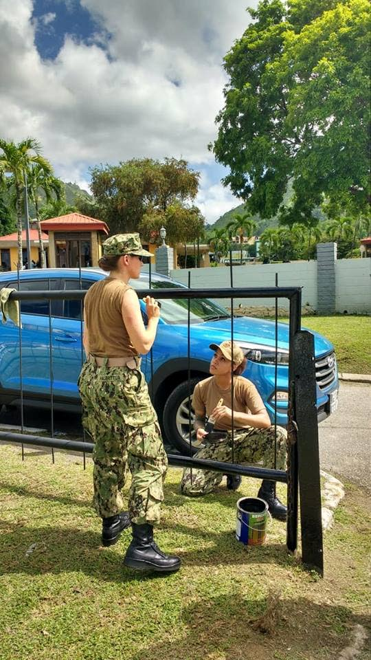 Captain of the USS Gunston Hall Commader Fiona Halbritter (left) chats with one of her personnel while painting the front gate of the Military Cemetery at Long Circular Road this morning as part of joint community relations event with the Trinidad and Tobago Defence Force.
