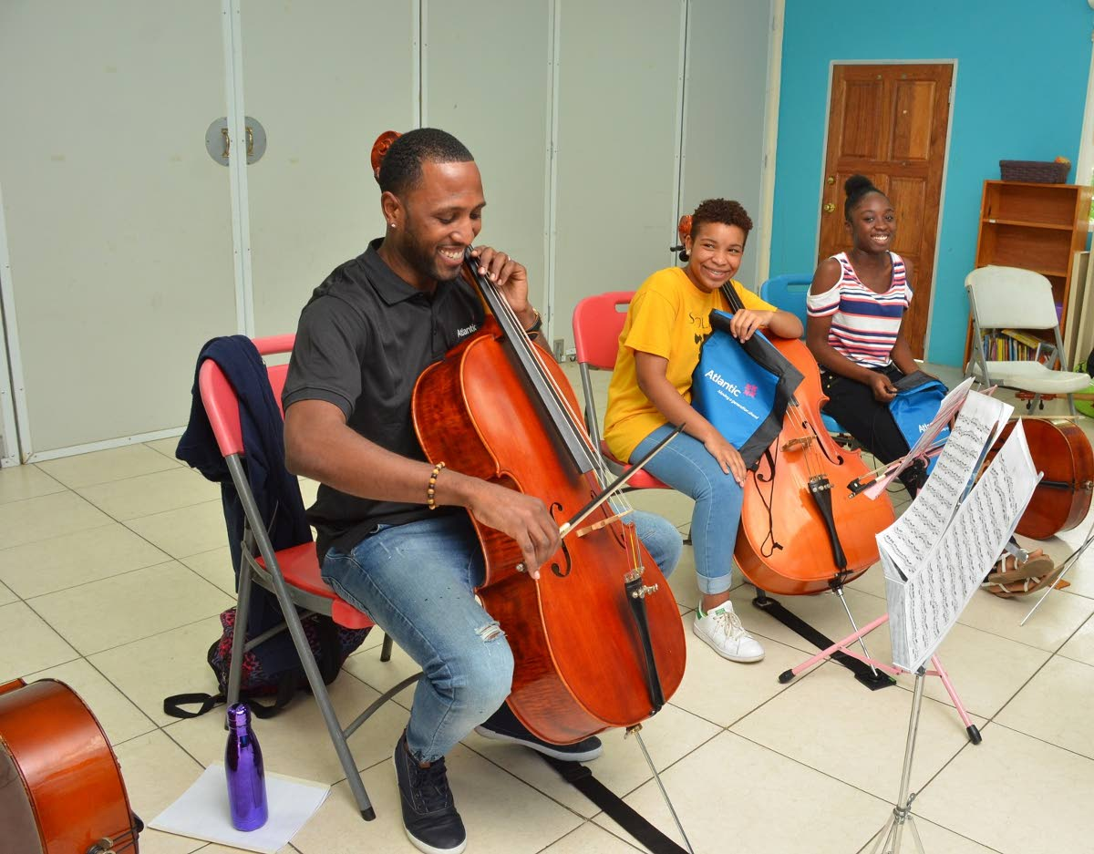 Olympic sprinter and Atlantic sports ambassador  Richard Thompson, left, learns to play the cello, encouraged  by Sarah Permel and Jazlyn Morris, members of the Trinidad   and Tobago Youth Philharmonic Orchestra.