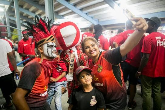 Digicel's 'Man of the Match' (centre) poses with three fans for a selfie, during Wednesday's CPL match between the Trinbago Knight Riders and the St Lucia Stars, at the Queen's Park Oval.