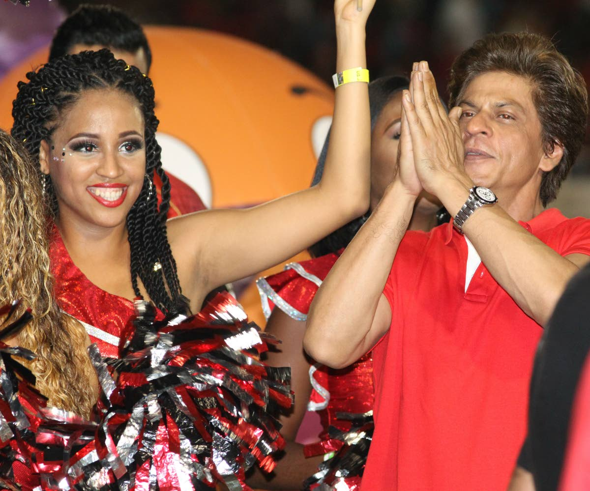 Star at the Oval: TKR co-owner Shah Rukh Khan gestures to fans alongside a cheerleader at Queen's Park Oval, Port of Spain on Friday night where he took in the match between TKR and Jamaica Tallawahs. PHOTO BY ANGELO MARCELLE