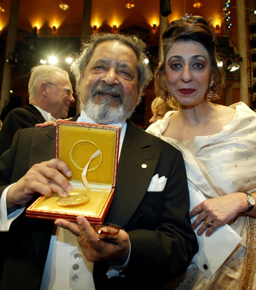 Nobel literature laureate Sir V S Naipaul, with his wife Nadira at his side, displays his medal after receiving it from the Swedish king at the Concert Hall in Stockholm, December 10, 2001.