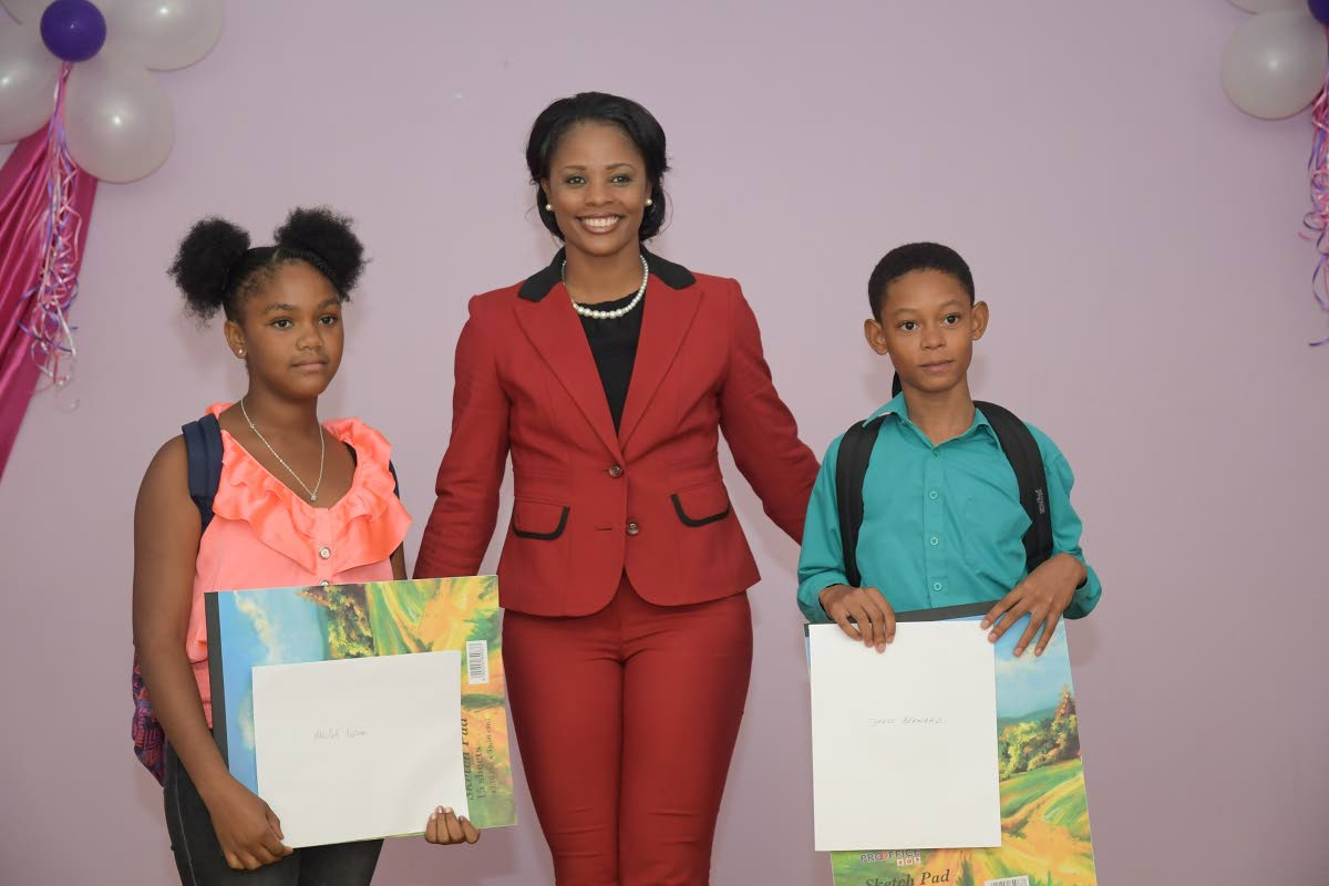 West Indies cricketer and Atlantic sports ambassador Merissa Aguilleira, centre, with Tyrese Bernard, right, and Akeelah Nelson, the top male and female SEA students of the Morgua district