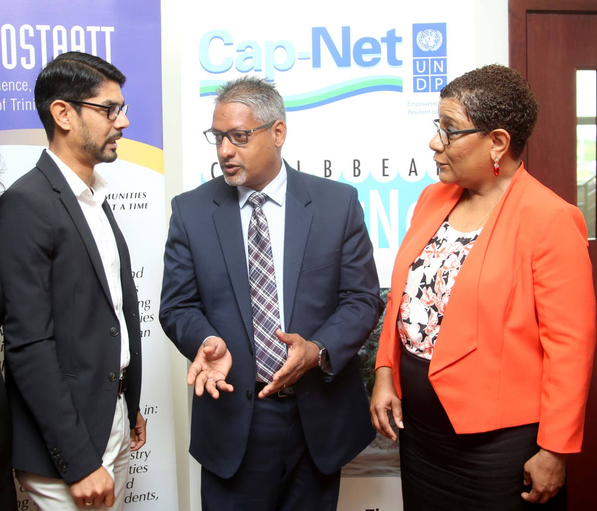 Agriculture Minister Clarence Rambharat (centre) speaks with Dr Ronald Roopnarine - network manager, Caribbean Waterfront Cap - Net UNDP and Dr Gillian Paul, president of COSTAATT at the opening ceremony of the Integrated Urban Flood Risk Mitigation and Management workshop.     PHOTO BY VASHTI SINGH