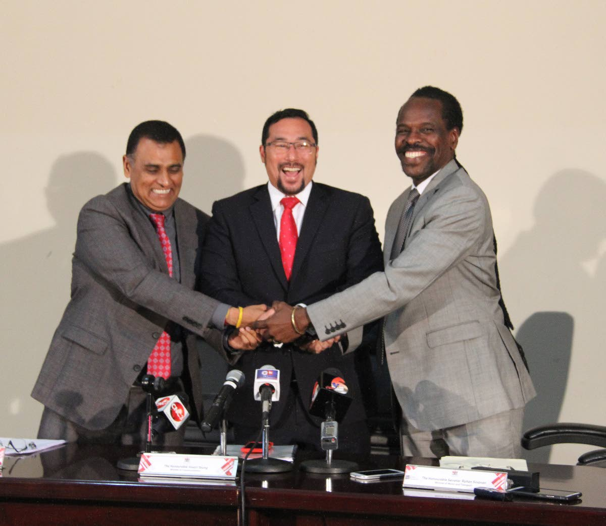 Works and Transport Minister Rohan Sinanan, National Security Minister Stuart Young and Ag Attorney General Fitzgerald Hinds join hands after a press conference yesterday at the Works and Transport ministry in Port of Spain.
