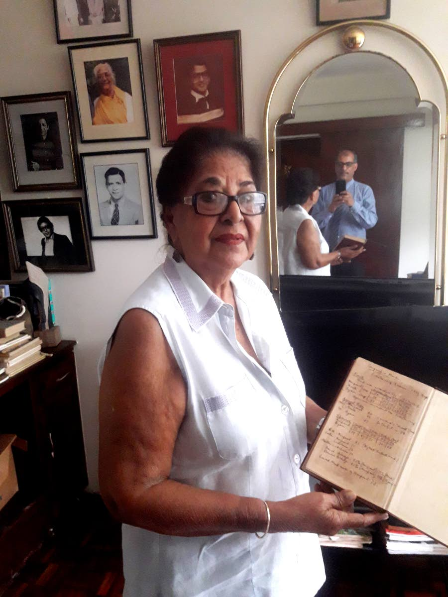 NO INFO: Savi Akal, sister of  Sir Vidia Naipaul shows off  a report book from Nailpaul's school days at Queens Royal  College.
