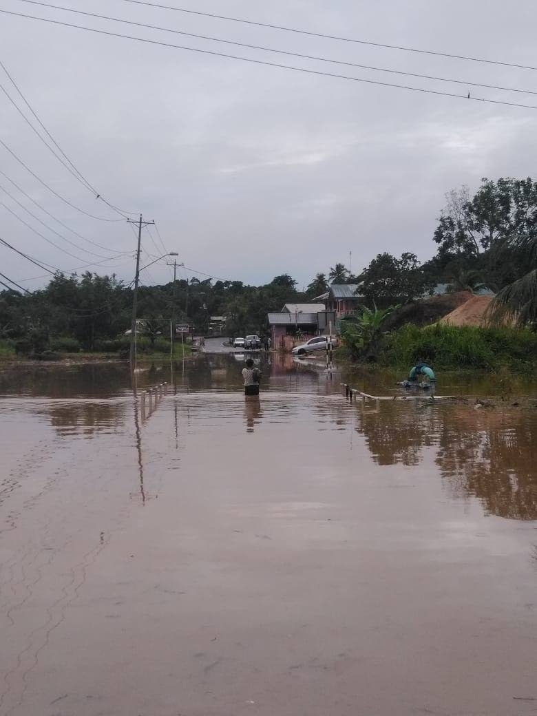 WADING: A woman walks over a flooded bridge in Caparo yesterday.   PHOTO BY SHARLENE RAMPERSAD