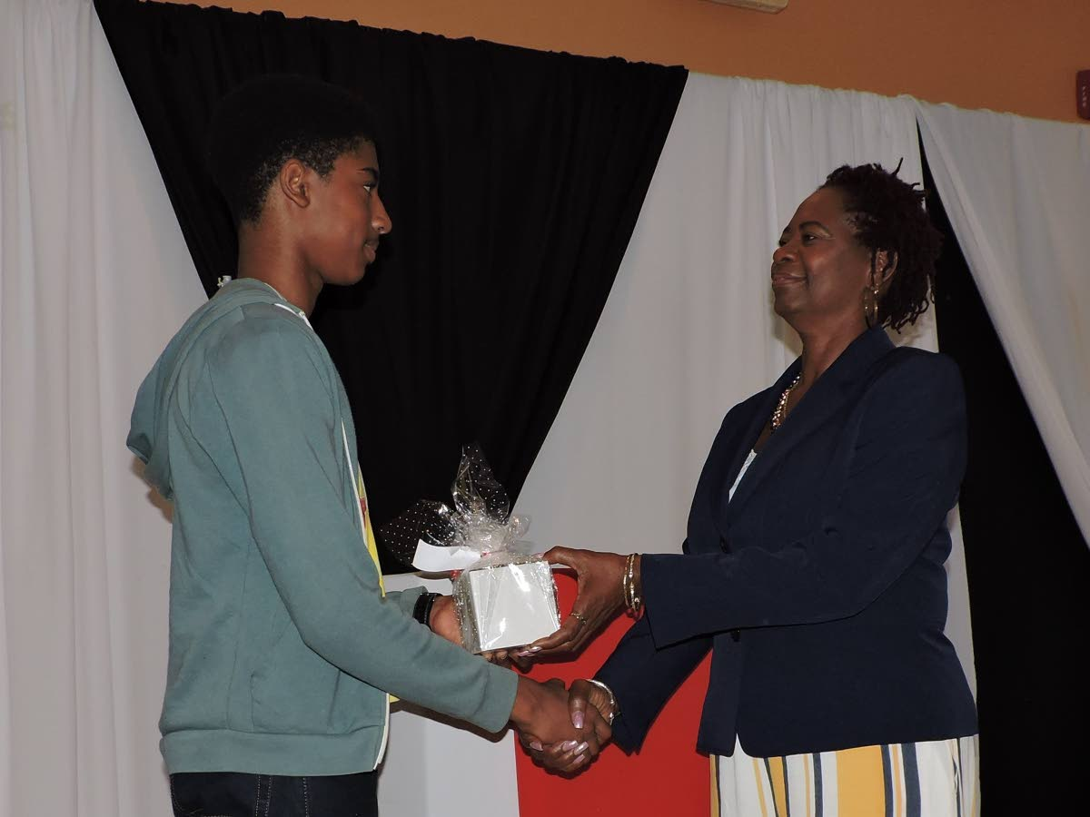Lois Leslie, right, Chief Executive Officer of E-iDCOT's is presented with a token of appreciation from a graduate at Friday's graduation exercise for 27 participants of the Tobago Young Innovators Camp at the Tobago Hotel and Tourism Institute (THTI) Conference Room in Mt St George.