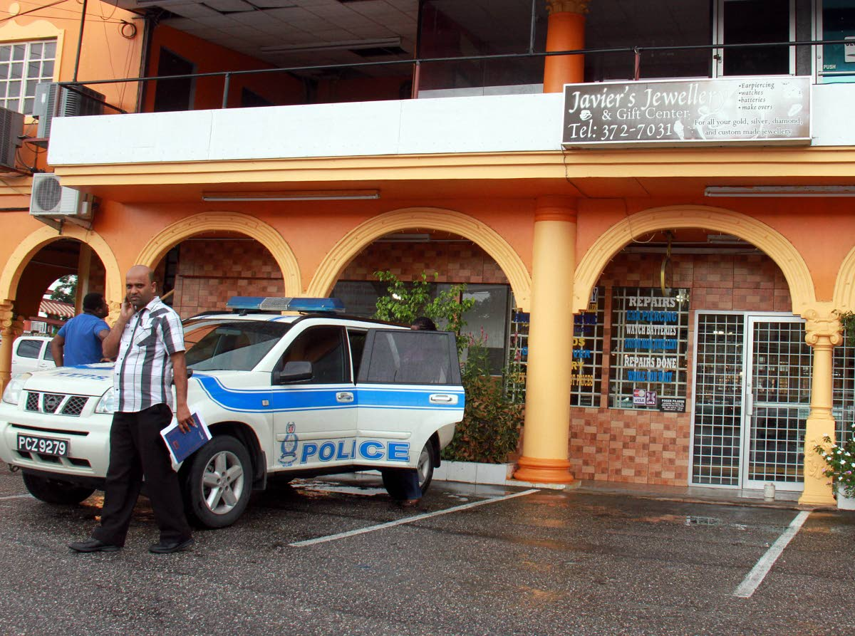 A police vehicle parked in front of Javier's Jewellery shop at the GN Shopping Centre in Penal after the owner Roger Pilgrim was shot during a robbery at the store. PHOTO BY ANIL RAMPERSAD