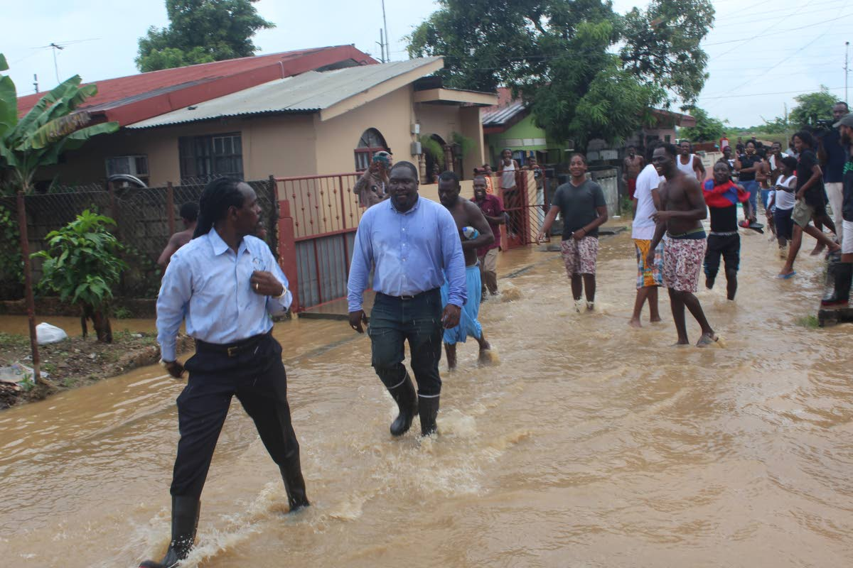 August 15, 2018: RUN, FITZ, RUN: Acting  Attorney General Fitzgerald Hinds runs away from Beetham residents after getting a dirty water bath yesterday. PHOTO BY ENRIQUE ASSOON
