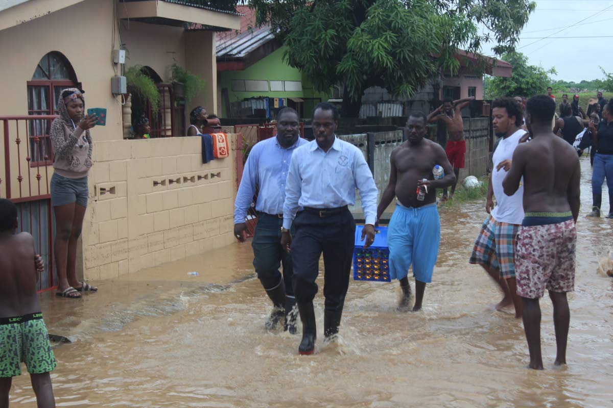Acting Attorney General Fitzgerald Hinds and Akil Audain walk through floodwaters among residents before being kicked at with the muddy water in Beetham Gardens last Tuesday. PHOTO by ENRIQUE ASSOON