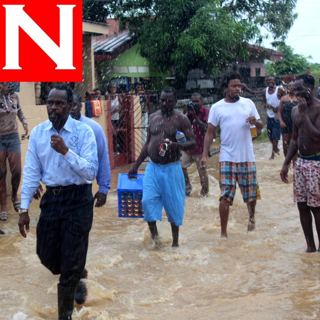 Acting Attorney General Fitzgerald Hinds walks hastily out of Beetham Gardens as group of men approach before dashing floodwater on him. PHOTO BY ENRIQUE ASSOON.