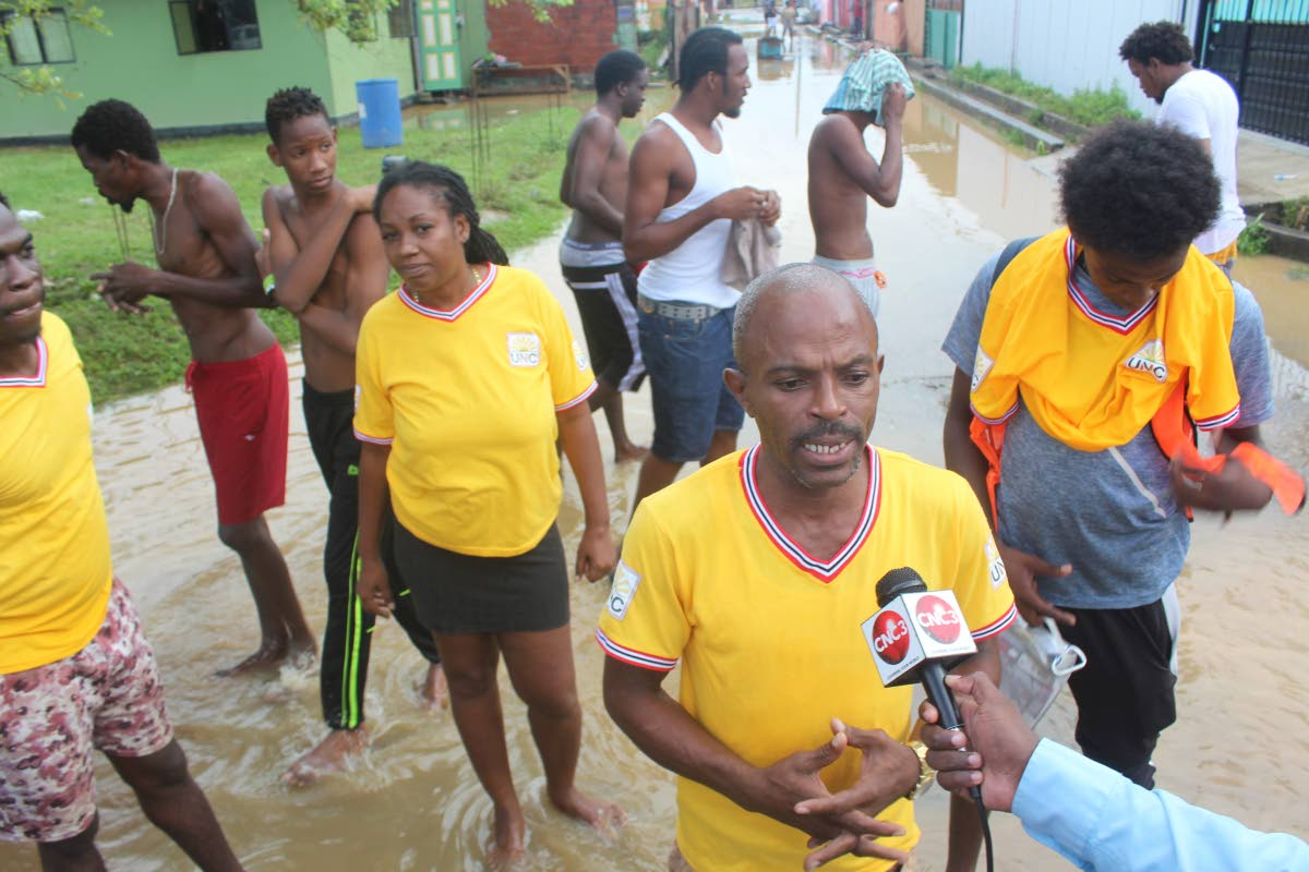 UNC activist Andersen Wilson (front) and a group of residents talk to the media on Tuesday after acting Attorney General and Laventille West MP Fitzgerald Hinds were chased out of the area. PHOTO BY ENRIQUE ASSOON