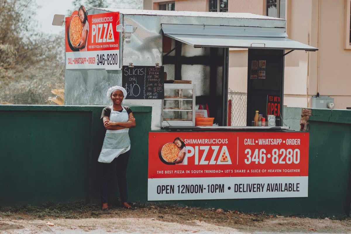 Shimone Anthony, 29, stands next to her mobile pizzeria, Shimmerlicious Pizza, Pt Sable Road, Pt D'or, La Brea.