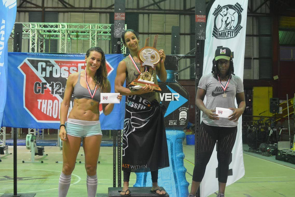 Champion of the Female Rx division, Lyndsay Murray, with her trophy at the third annual International CrossFit12-12-12 Throwdown, which was held at the Woodbrook Youth Facility on Saturday. Amanda Morris of Barbados, right, placed second and Yvette Tromp of Aruba took third.