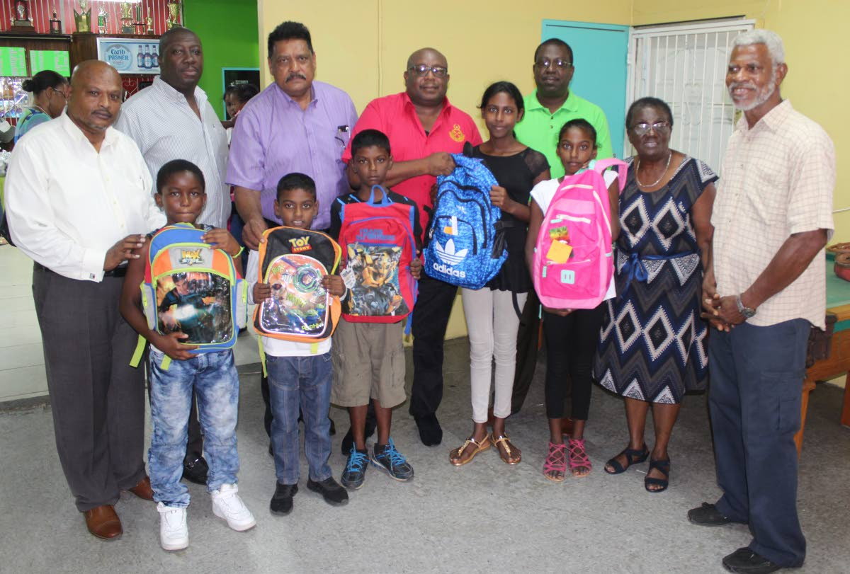 Krishna Bedassie, (at back left to right), Hayden Walcott, acting deputy Prisons Commissioner Mookish Pulliah, acting Prisons Commissioner Dane Clarke, Sherwin Bruce, Pastor Cynthia Cardogan and her husband with  several children who received backpacks with school supplies at Prisons Sports Complex, Arouca yesterday. PHOTO BY ENRIQUE ASSOON