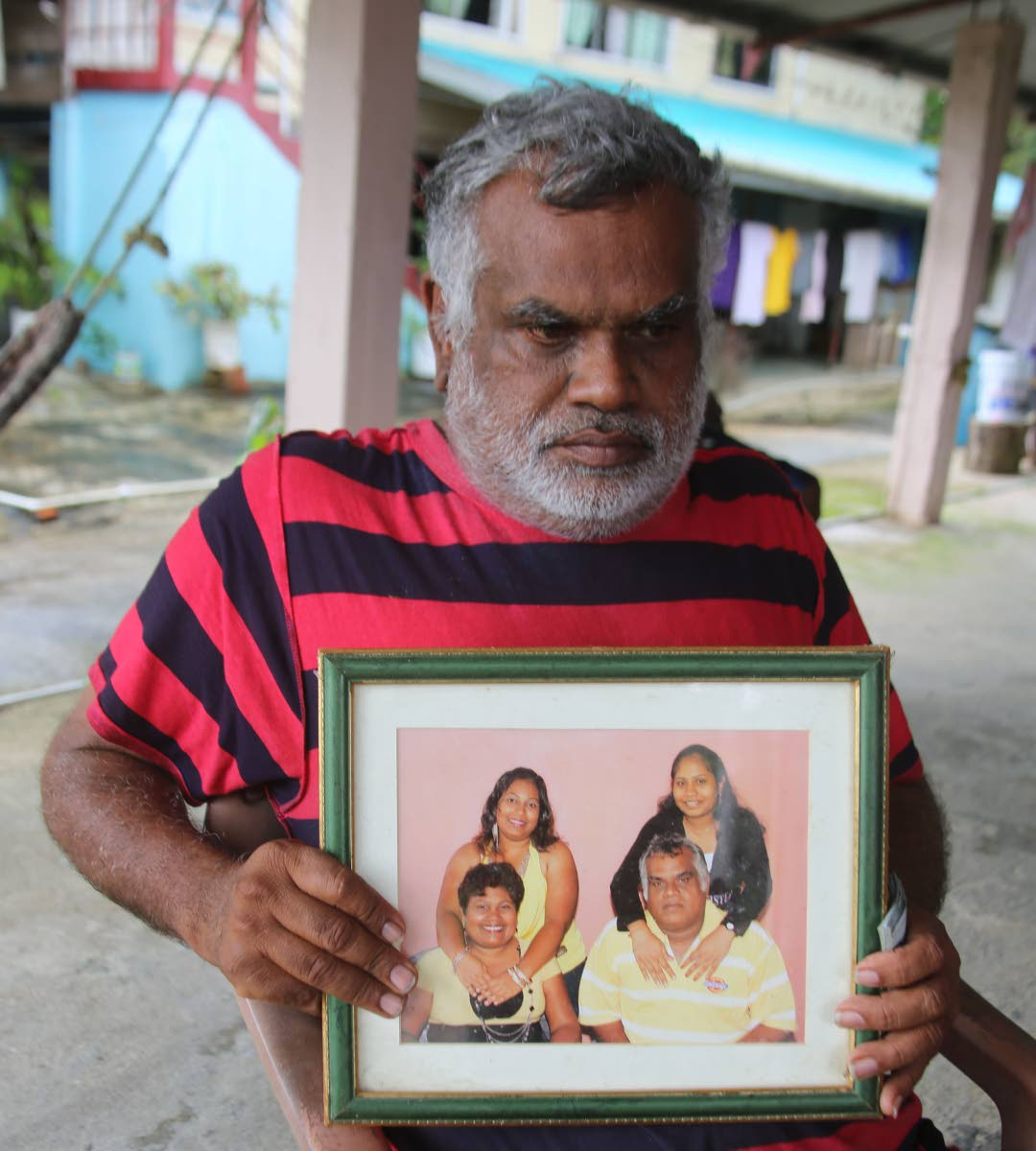 Rajendra Basdeo holds a family photo with his wife Lutchmin Rampersad-Basdeo and daughters Aarti and Annurada at his home in Rousillac yesterday. Lutchmin and Aarti died in a car crash on Friday.