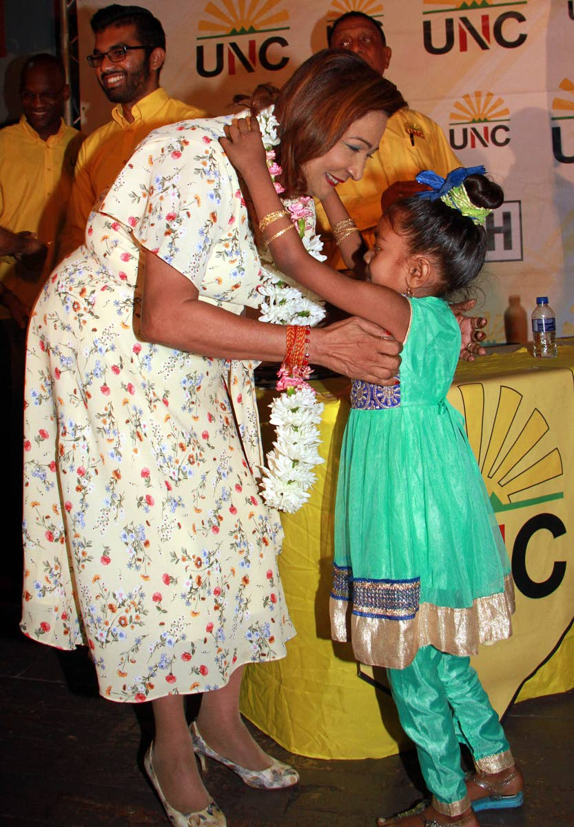Flowers for Kamla: Opposition Leader Kamla Persad-Bissessar receives a garland from six-year-old Christine Seelel during the UNC's Monday Night Forum at Chaguanas South Secondary School. PHOTO BY ANIL RAMPERSAD.