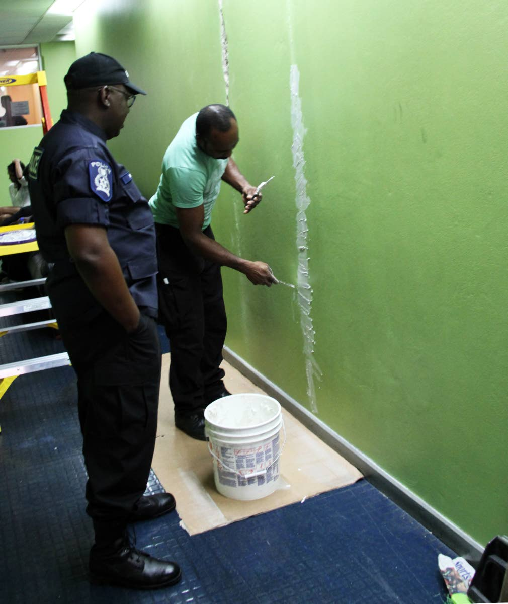 MASON COP: A policeman looks on as his colleague from the Police Service's facilities management department repairs cracks in a wall caused by Tuesday's earthquake at the Police Administration Building in Port of Spain yesterday.   PHOTO BY SUREASH CHOLAI