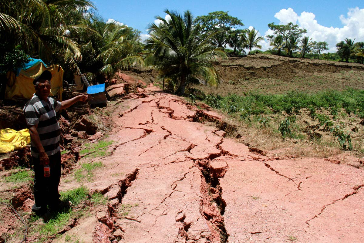 Farmer Nobbie Mathura points to the huge cracks in the Los Iros Hillview Road and his garden after Tuesday's earthquake.