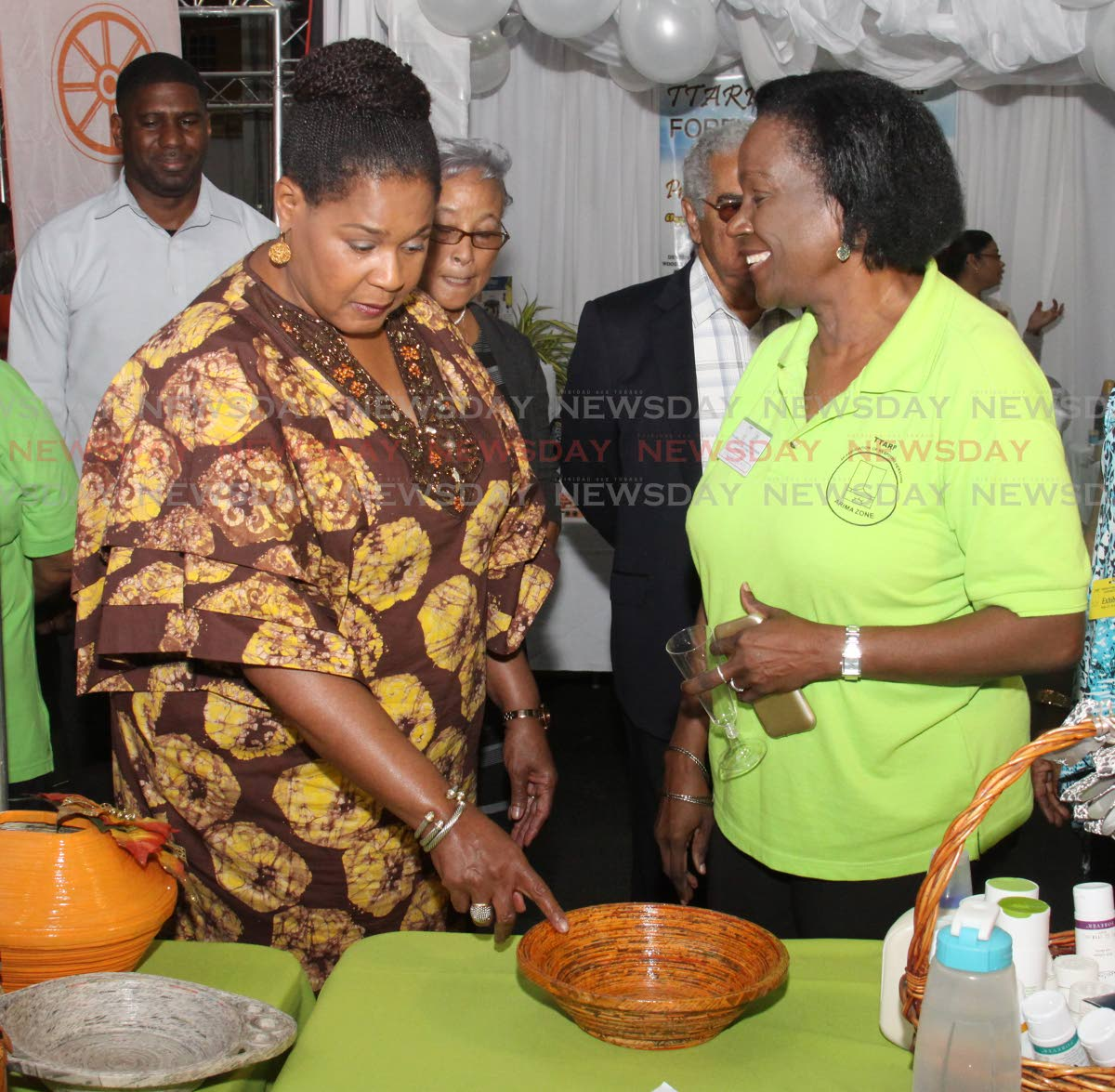 Bowled over: President Paula-Mae Weekes, left, questions Sandra Sydney, a zone representative from the Association of Responsible Persons Eastern Angels, Arima, about her paper bowl art at the TTARP 25th anniversary expo, Centre of Excellence, Macoya yesterday. PHOTO BY ANGELO  MARCELLE