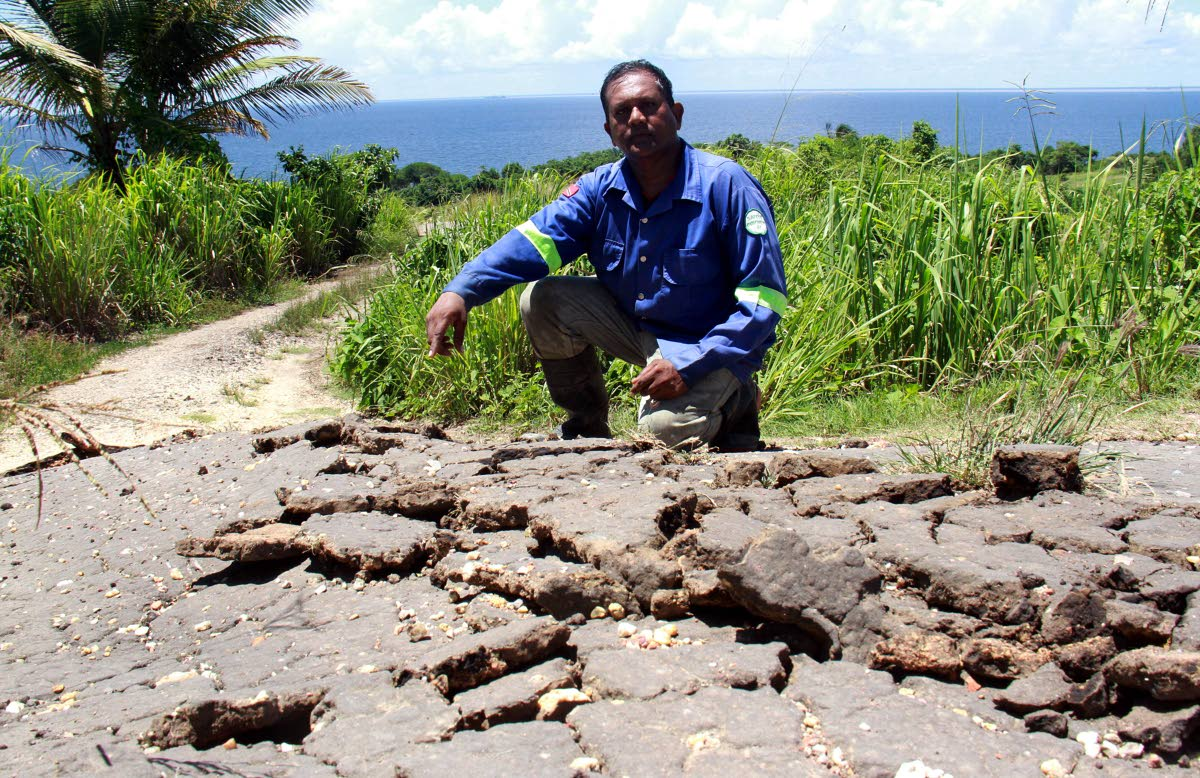 File photo: Farmer Kumar Dwarika points to one of the damaged access road caused by the earthquake  in Los Iros. PHOTO BY ANIL RAMPERSAD.