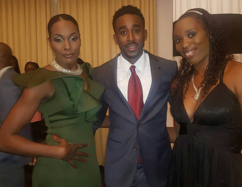 National volleyballers Jalicia Ross,left, and Kelly-Anne Billingy,right, pose for a picture with 400m hurdler, Jehue Gordon,at the Diplomatic Centre, St Ann's, during  a function hosted by Prime Minister Dr Keith Rowley, for TT athletes who competed at the recent CAC Games, in Colombia.